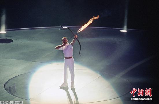 """资料图:37岁的安·雷波略在离焰塔70米处用弓箭将火把射出,""""射燃""""了21米高塔上火炬台,点燃奥运圣火。"""