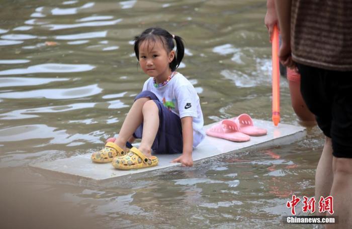 7月21日,郑州,暴雨造成城区内部分路段积水,小女孩坐在木板上。 图片来源:视觉中国