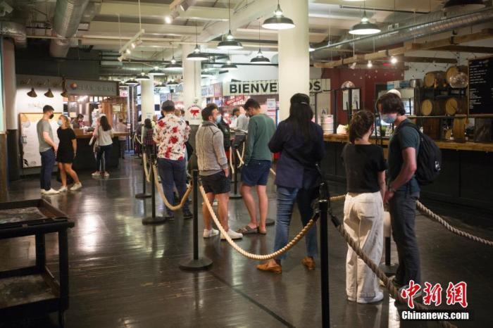 资料图:当地时间5月25日,顾客在美国纽约切尔西市场一家餐厅排队购买餐食。自5月下旬纽约州博物馆、电影院、餐厅、零售业等商业和文化场所的客容量限制全面解除后,纽约著名的切尔西市场客流逐渐恢复。 中新社记者 廖攀 摄
