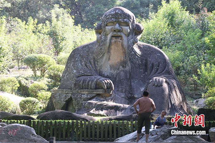 图为7月9日,一名小朋友在家长的带领下在老君岩造像下玩耍。 <a target='_blank' href='http://www.chinanews.com/'>中新社</a>记者 蒋启明 摄