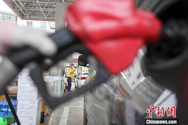 资料图:工作人员给车辆加油。 /p中新社记者 张云 摄