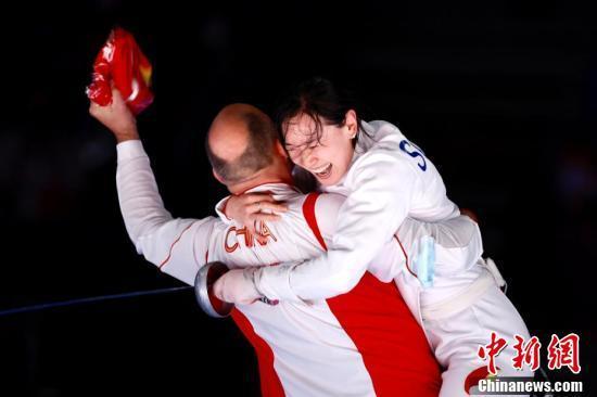 7月24日晚,东京奥运会女子重剑个人赛结束了决赛的较量,中国选手孙一文以11:10战胜罗马尼亚选手波佩斯库,夺得冠军。图为孙一文夺冠后和团队成员一起庆祝。<a target='_blank' href='http://www.chinanews.com/'>中新社</a>记者 富田 摄