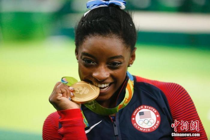 资料图:美国体操运动员拜尔斯咬着金牌。杜洋 摄