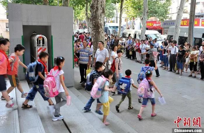 资料图:武汉一小学门外等待学生放学的家长们。中新社发 张畅 摄