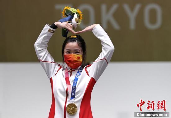 7月24日举行的东京奥运会女子10米气步枪决赛中,中国选手杨倩夺得冠军,为中国代表团揽入本届奥运会第一枚金牌。图为杨倩在领奖台上比出爱心手势。