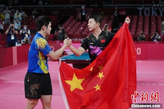 """7月30日晚,东京奥运会乒乓球男单决赛迎来中国选手""""内战""""。最终马龙以4:2战胜樊振东,成功卫冕冠军。这是中国代表团在本届奥运会的第19金。图为马龙与樊振东赛后举国旗致意。<a target='_blank' href='http://www.kedivino.com/'>中新社</a>记者 韩海丹 摄"""