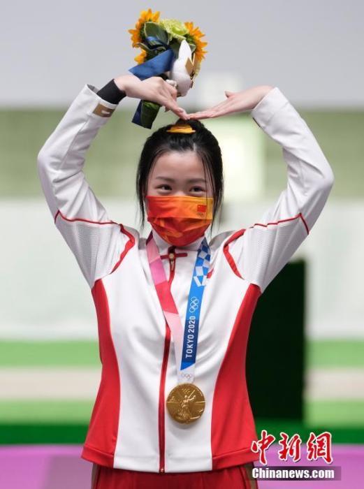 7月24日举行的东京奥运会女子10米气步枪决赛中,中国选手杨倩夺得冠军,为中国代表团揽入本届奥运会第一枚金牌。这也是本届东京奥运会诞生的首枚金牌。图为杨倩在领奖台上比出爱心手势。中新社记者 杜洋 摄