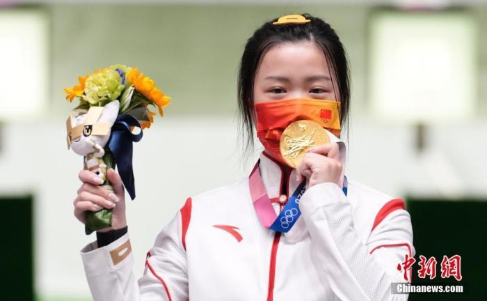 7月24日举行的东京奥运会女子10米气步枪决赛中,中国选手杨倩夺得冠军,为中国代表团揽入本届奥运会第一枚金牌。这也是本届东京奥运会诞生的首枚金牌。图为杨倩隔着口罩亲吻金牌。中新社记者 杜洋 摄