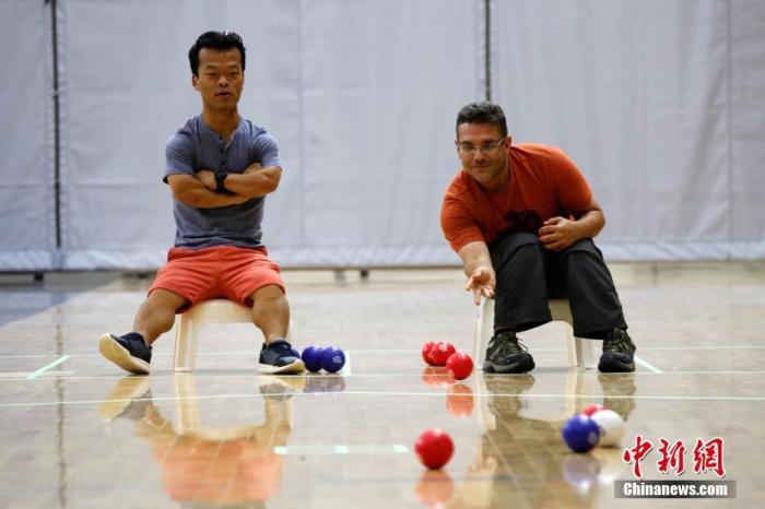 资料图:两名运动员在比赛间歇进行室内硬地滚球练习。 中新社记者 余瑞冬 摄