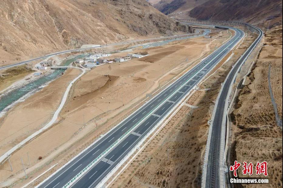 """资料图:航拍西藏""""三路""""同框,画面从左至右分别是青藏公路、拉萨至羊八井高等级公路和青藏铁路。 江飞波 摄"""