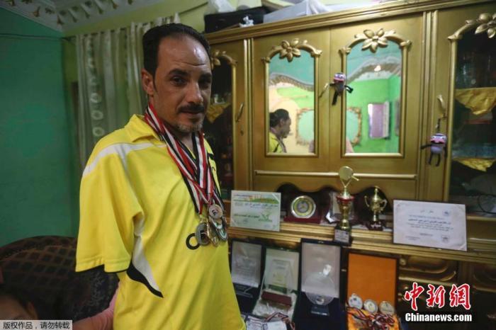资料图:埃及开罗,哈马托在家中将自己赢得过的奖牌挂在脖子上。