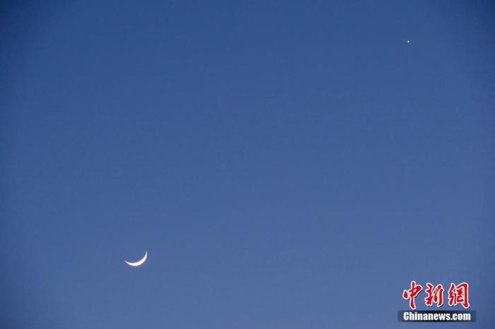 """资料图:此前,北京,天气晴好,太阳落山之后,天宇""""金星合月""""天文景观清晰可见。中新社记者 孙自法 摄"""
