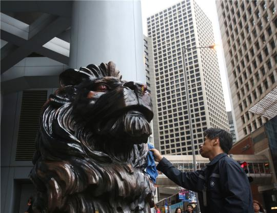 A worker cleans the lion sculpture that was vandalized by rioters outside an HSBC Bank branch in Hong Kong on Thursday. (China Daily/PARKER ZHENG)