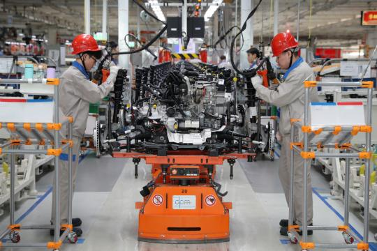 FAW-Volkswagen employees work on an assembly line at the automaker's Tianjin plant. [Provided to China Daily]