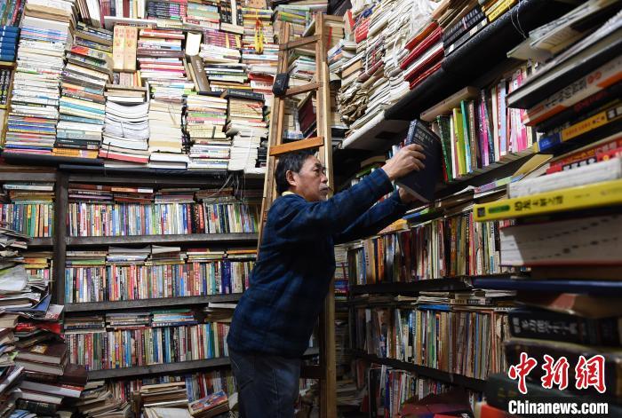 图为旧书店的老板王米瑜正在整理书籍。 周毅 摄