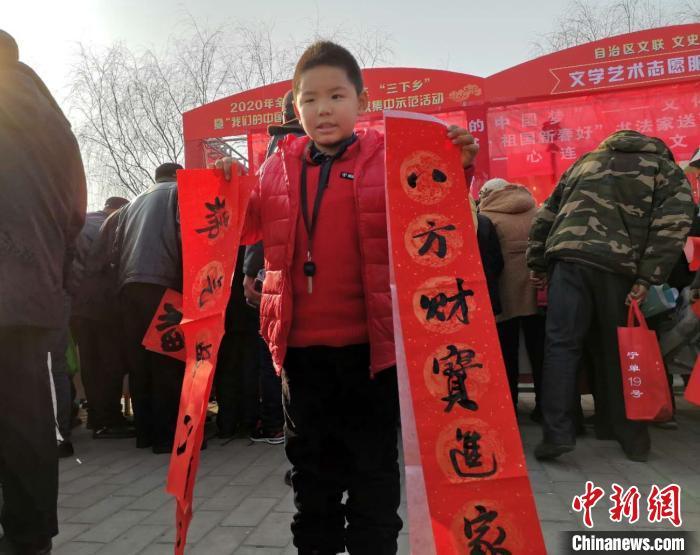 小朋友展示书法家协会成员为其写的春节对联。 李海龙 摄
