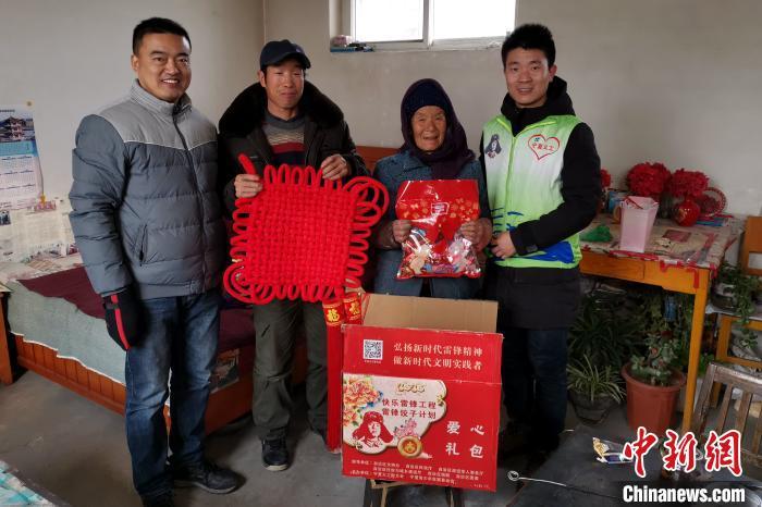 """受助家庭看到送来的""""雷锋饺子""""礼包和漂亮的中国结,眼里心里都是笑意。 陈芳妍 摄"""
