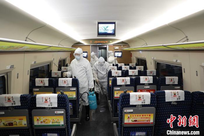 侯峰(右一)和同事一起为动车组列车消毒。 邢星 摄