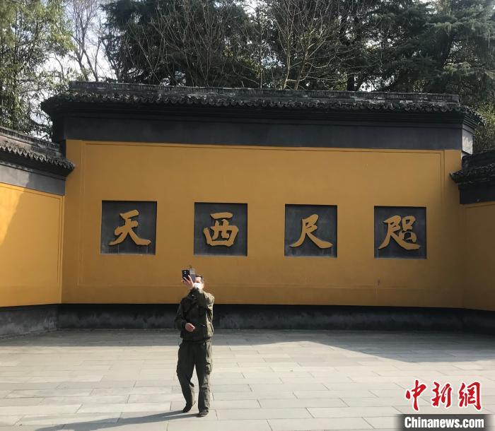 图为杭州灵隐飞来峰景区大门口,一位游客在自拍。 严格 摄