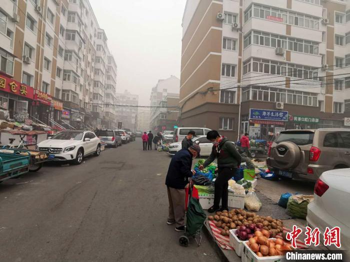 4月18日上午,哈尔滨市民在雾霾中购物。 姜辉 摄