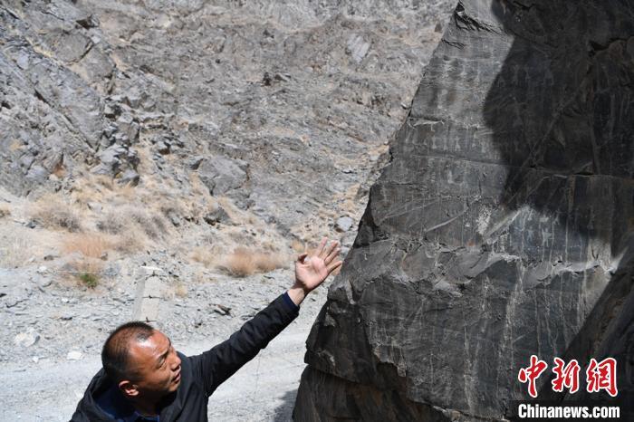 """在一处用铁丝网周围的岩体上,有一幅被称作""""巨型舞蹈图""""的岩画。 杨艳敏 摄"""