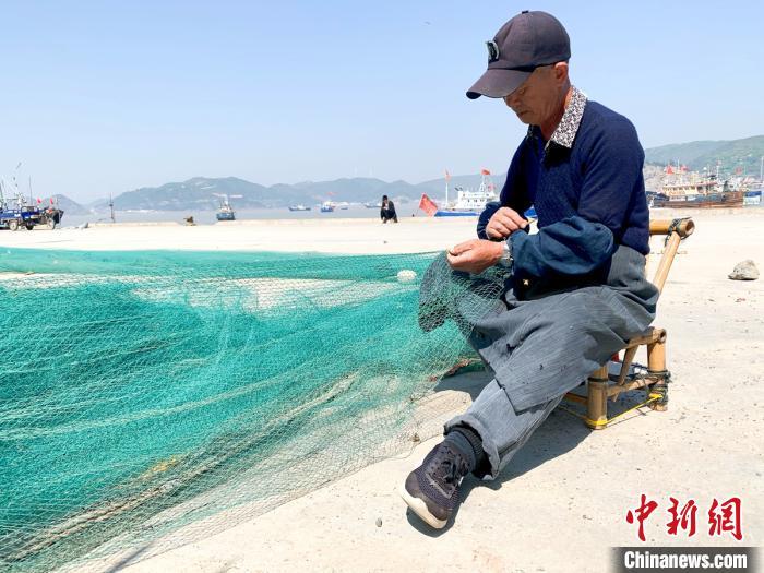 浙江台州玉环坎门中心渔港内,渔民正在修补渔网 吕琼雅 摄