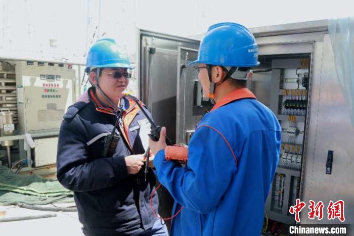 图为±800千伏青南换流站内李生龙(左)正在与施工方沟通设备验收事宜。 董庆芳 摄