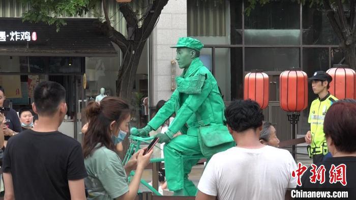 """图为西安大唐不夜城行为艺术演员马龙""""化身""""雕塑。 党田野 摄"""