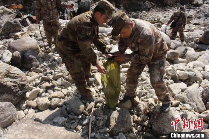 图为西藏军区某旅炮兵营官兵为强嘎村清理河道。 牛思佳 摄