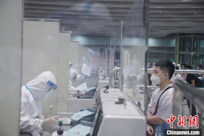 北京恢复国际直航首日,北京边检总站工作人员为入境旅客办理入境手续。 北京边检总站供图 摄