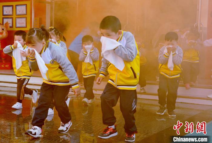 """11月5日,江西省德兴市铜矿中区幼儿园的小朋友,在老师的引导下,捂住口、猫着腰迅速撤离""""火灾""""现场。 卓忠伟 摄"""