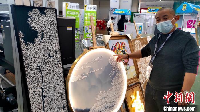 福建泉厦漳油画设备供应商负责人欧阳晖勇,向记者介绍由新材料、新技术智能制造而成的装饰画。 杨伏山 摄