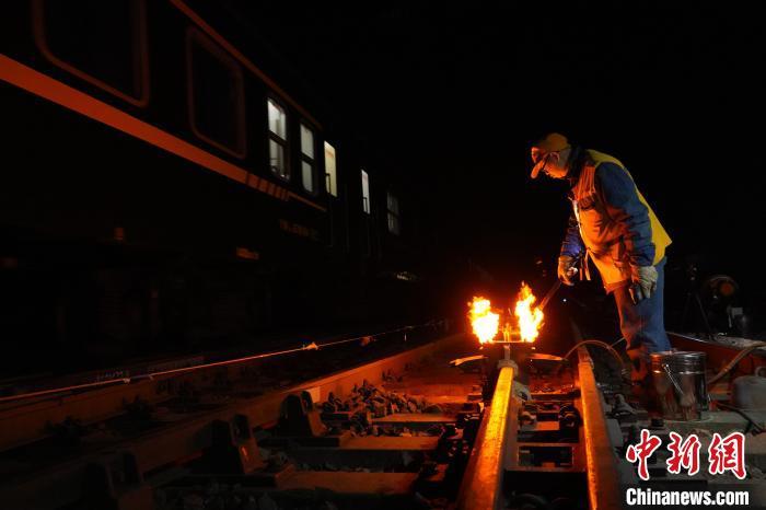 图为铁路工人对更换的道岔轨道进行焊接。 阚力 摄