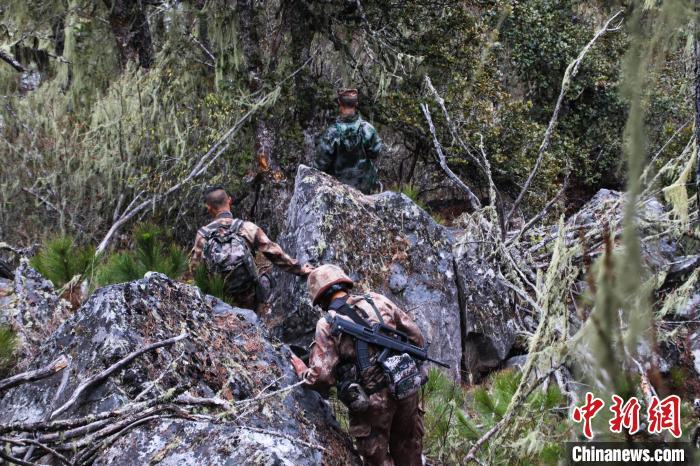 图为官兵们穿越巨石头丛。 张洋 摄