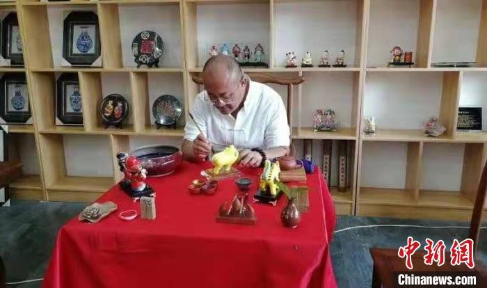 29日,山西省长治市黎城县一间工作室内,46岁的张学义手拿画笔,细致地刻画老虎造型。黎城县融媒体中心供图