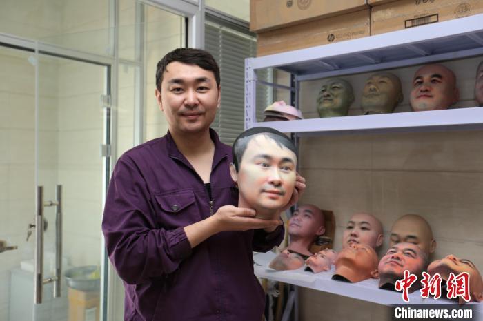 西安市殡仪馆整容组工作人员展示自己的面部3D打印模型。 张远 摄