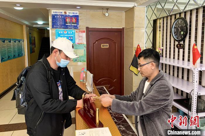 店主韩永亮(右)为顾客办理入住。 李佩珊 摄