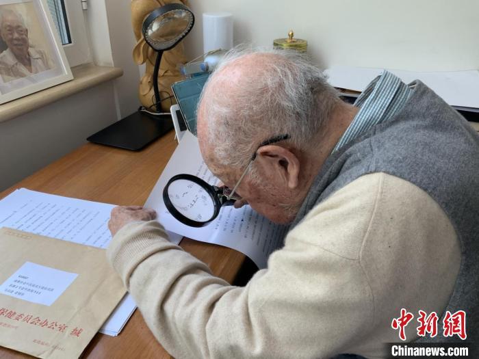 马识途用放大镜核查书稿。(四川人民出版社 供图)