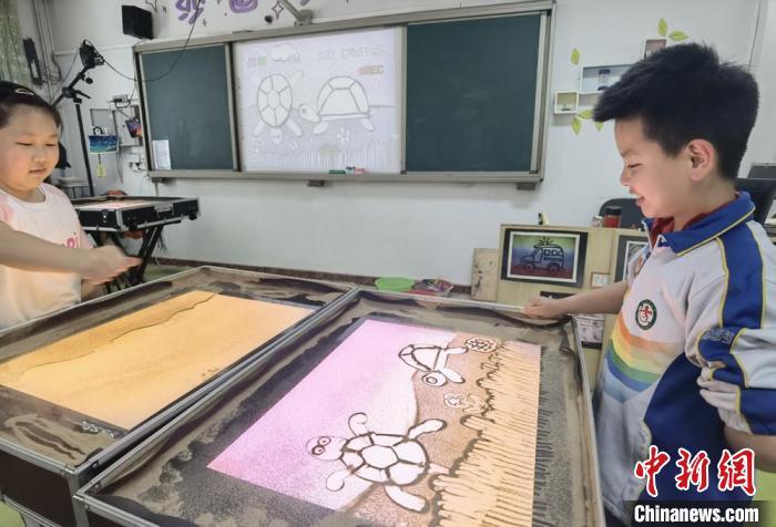 图为七里河小学学生创作沙画。 高展 摄