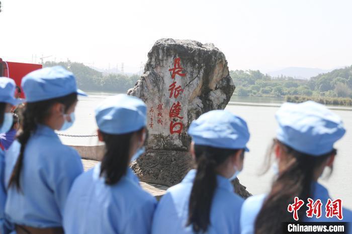 图为一群身着红军服的学生在长征第一渡口前开展研学教育活动。 刘力鑫 摄
