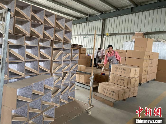 图为,庄寨镇一工厂工人正在打包棺木。 孙宏瑗 摄