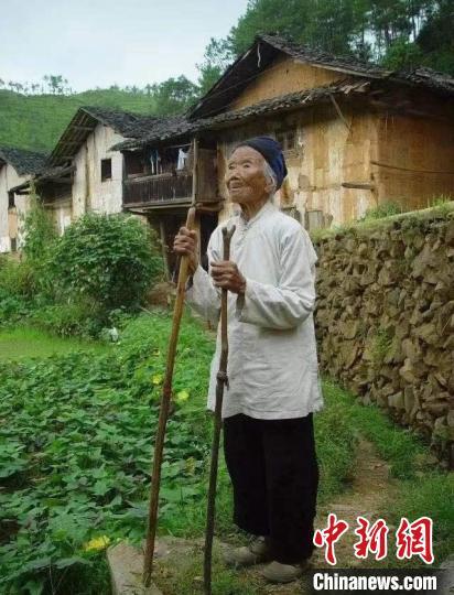 图为池煜华老人站在老屋前。 兴国县委宣传部 摄