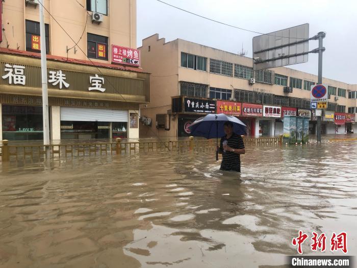 洞桥镇居民行走在积水中。 林波 摄