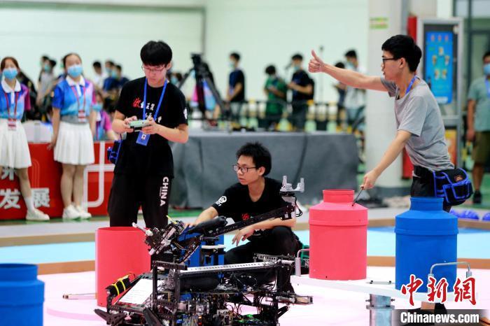 比赛选手正在适应场地,对机器人做最后的调试。 梁犇 摄
