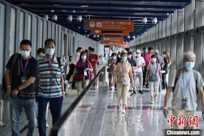 """游客正从香港启德邮轮码头前往首班复航的星梦邮轮""""云顶梦号""""。 李志华 摄"""