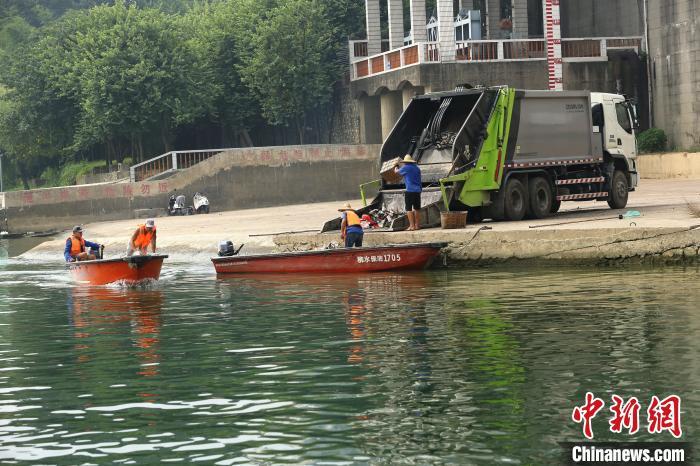 水上保洁大队工作人员将垃圾放进垃圾车。 朱柳融 摄