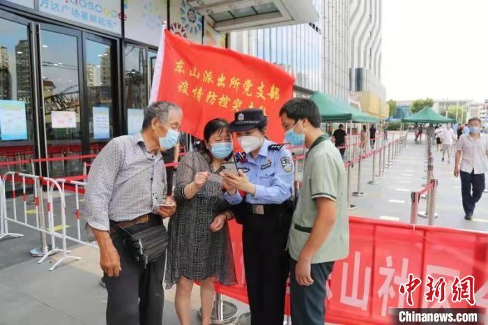 图为警方指导市民查询行程码。 潘冉东 摄