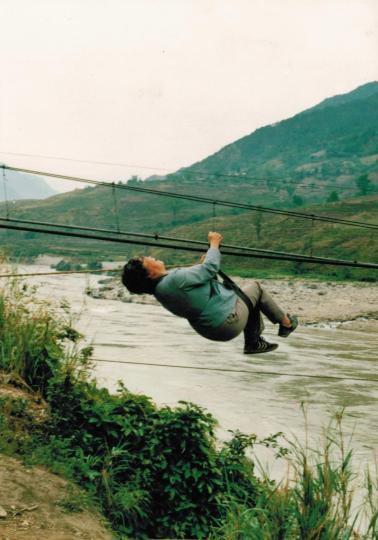资料图:李桓英坐索道过河。 首都医科大学附属北京友谊医院、北京热带医学研究所供图