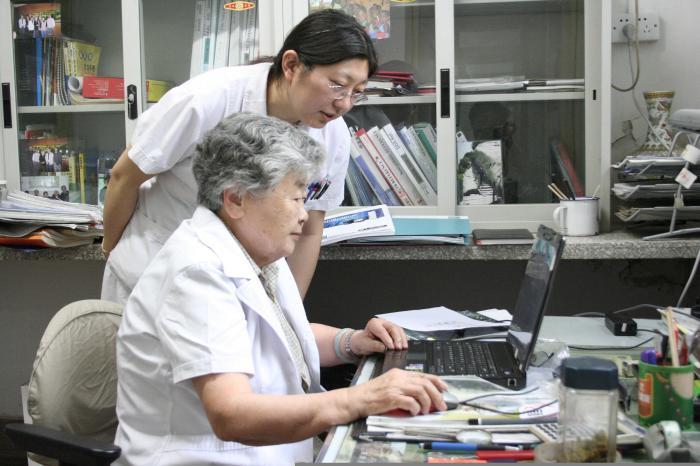 李桓英与助手在工作。 首都医科大学附属北京友谊医院、北京热带医学研究所供图