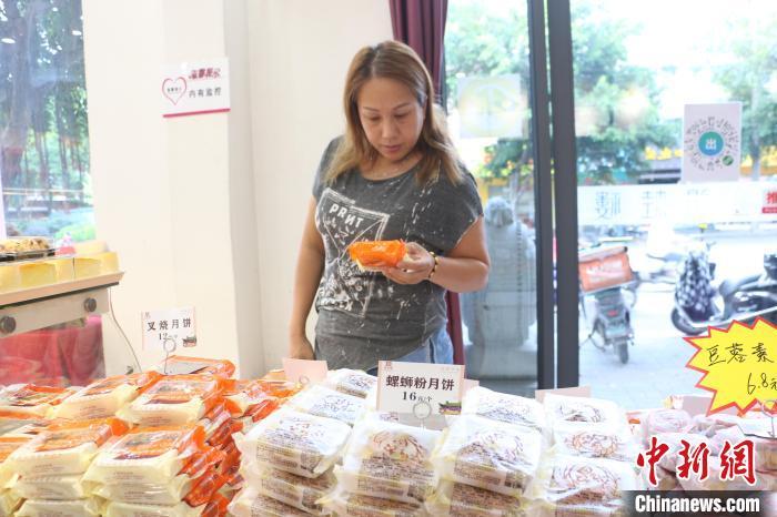 民眾在商店選購螺螄粉月餅?!×周?攝